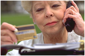 Picture of woman on the phone looking at her credit card