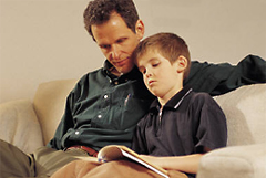 photo of a father and son looking at a book